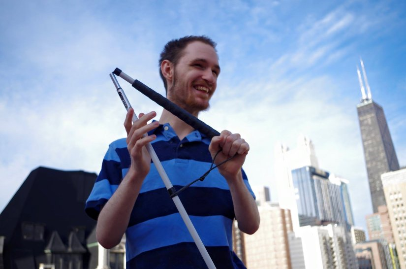 Image of a young man smiling against the backdrop of a city. He is holding a white cane and wearing a striped black and blue shirt.